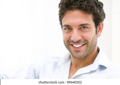 Closeup of happy young man looking at camera at home