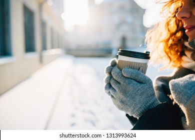 Close-up of happy young woman drinking coffee outside in city, sun shining through her hair. Female's hands in warm gloves holding paper cup hot drink in winter day.