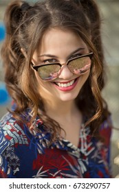 Close-up of a happy young woman wearing sunglasses