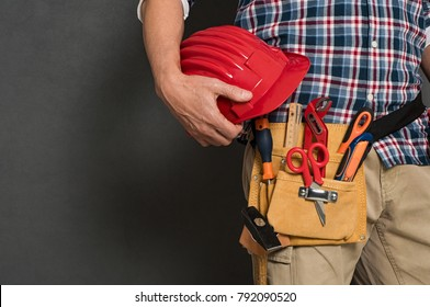 Closeup of hardhat held by construction worker on grey background. Bricklayer holding red helmet and kit tool. Closeup of craftsman hand holding tool belt with equipment on grey wall with copy space.