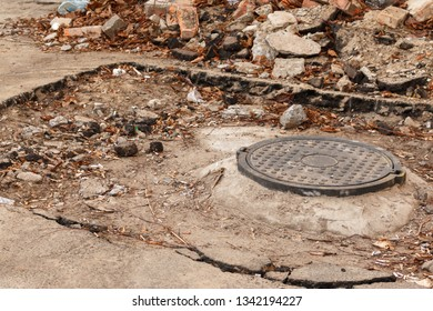 close-up of hatch on the dirty construction site during the renovation of asphalt pavement. manhole in the asphalt pit with cigarette butts against the background of stones and debris, toned image
