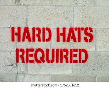 "Closeup of ""Hard Hats Required"" in red capital letters stenciled on wall of concrete blocks on construction site, for themes of safety and necessity"