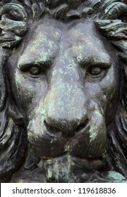 A Closeup Of The Head Of A Bronze Statue Of A Lion