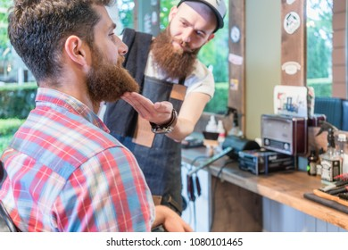 Close-up of the head of a redhead bearded young man ready for a trendy haircut under the guidance of a dedicated hairstylist