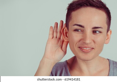 Closeup head shot macro face young nosy woman hand to ear gesture carefully intently secretly listening juicy gossip conversation news isolated green gray wall background Human face expression emotion