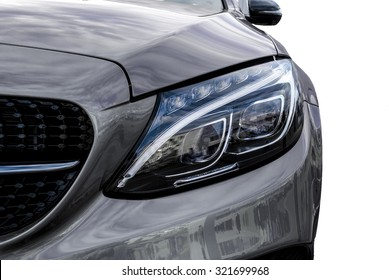 Closeup headlights of grey car and Car exterior detail with White back. Closeup headlights of car. Modern luxury car close-up banner background. Concept of expensive, sports auto Closeup headlights