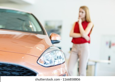 Closeup of headlights of new orange automobile in car dealership. Thoughtful female  customer with hand near chin on background standing and examining vehicle before buying. New purchase concept.