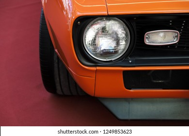 Closeup headlights of an orange retro car. Muzzle cars, bumper and the appearance of muscle car.