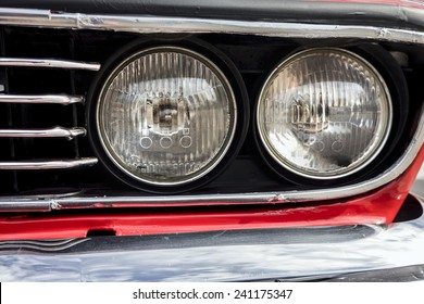 Closeup of the headlights of a red classic car.