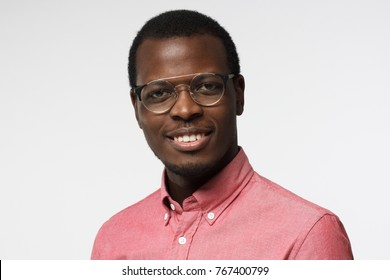 Closeup headshot of African American entrepreneur standing in red shirt against white background wearing round spectacles, smiling with satisfaction and confidence showing devotion to his business