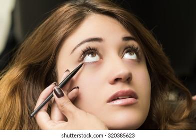 Closeup headshot brunette getting makeup treatment by professional stylist applying eyeliner.