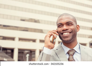 Closeup headshot handsome happy laughing young businessman talking on mobile phone outdoors. Instagram filter effect. Positive human emotions face expression