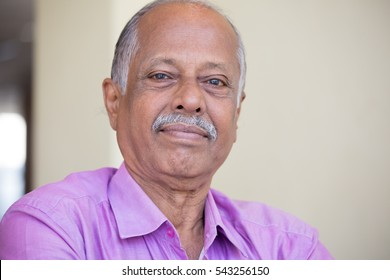 Closeup headshot portrait of elderly gentleman sitting down in pink shirt smiling, content, isolated indoors white wall background