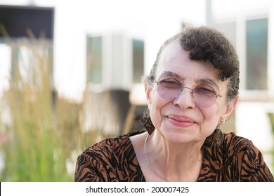 Closeup headshot portrait, grandmother with glasses, smiling, isolated outdoor background