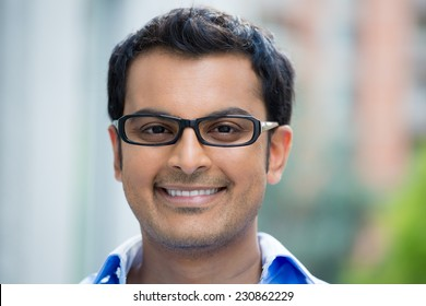 Closeup headshot portrait, happy handsome businessman, wearing black glasses relaxing outside of his office during sunny day, isolated on a blurred city urban background.