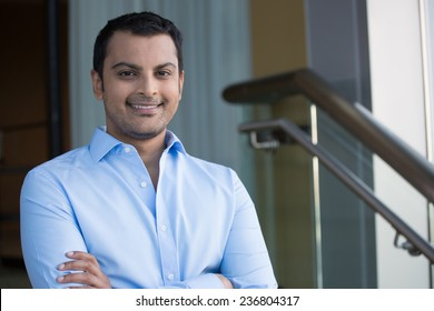 Closeup headshot portrait, happy handsome business man, smiling, arms crossed in blue shirt,confident and friendly on isolated office interior background. Corporate success