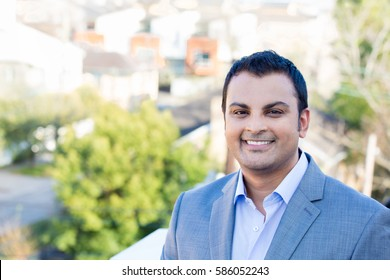 Closeup headshot portrait, happy handsome business man, smiling, in gray suit blazer,confident and friendly, isolated outdoors outdoors background. Corporate success