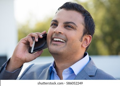 Closeup headshot portrait, happy handsome businessman in gray suit blazer, laughing during phone conversation, isolated outdoors outside background