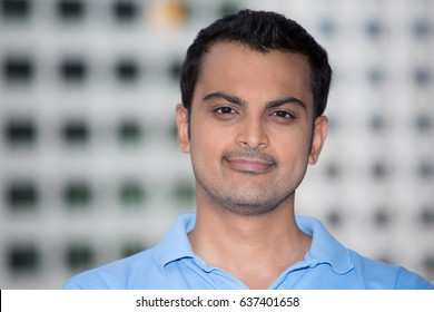Closeup headshot portrait, happy handsome business man, smiling, in light blue polo shirt, confident and friendly, isolated white building background. Corporate success