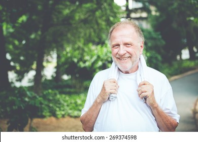 Closeup headshot portrait of happy  senior mature man, grasping towel around neck, isolated green trees foliage background. Positive human emotions, facial expressions. Retro faded vintage look