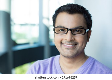 Closeup headshot portrait, smiling happy handsome man in purple sweater v-neck, wearing black glasses, isolated inside office background.
