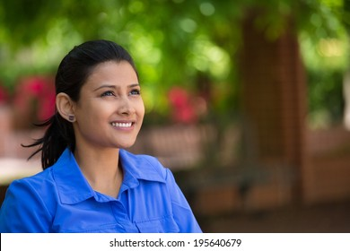 Closeup headshot portrait young beautiful happy business woman in blue shirt, sitting on bench, isolated green trees, nature background. Positive human emotion facial expression feelings