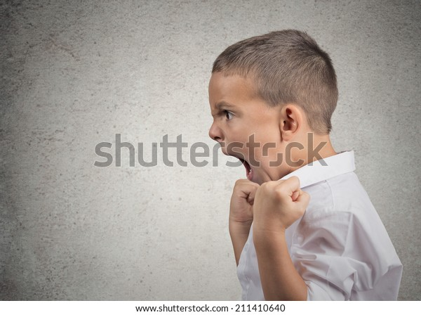 Closeup Headshot side view Portrait Angry Child Screaming, fists up in air isolated grey wall background. Negative Human face Expressions, Emotion, Reaction, Perception. Conflict confrontation concept
