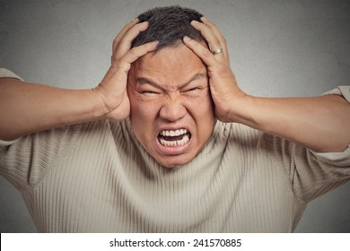 Closeup headshot stressed guy isolated on grey wall background. Human face expression emotions feelings