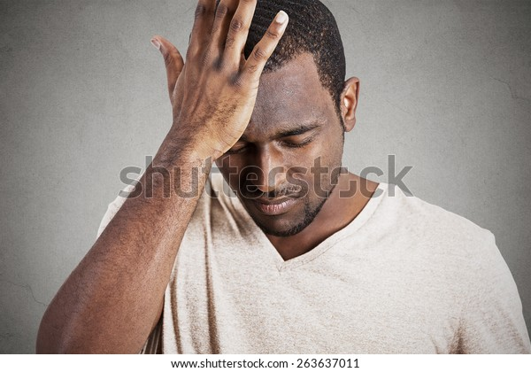 Closeup headshot very sad depressed, stressed, alone, disappointed gloomy young man head on hands having suicidal thoughts isolated grey wall background. Human emotion facial expression reaction
