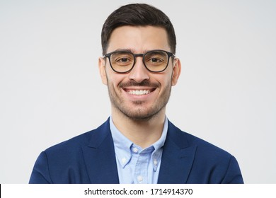 Close-up headshot of young businessman wearing glasses and smart casual suit, smiling at camera, isolated on gray background