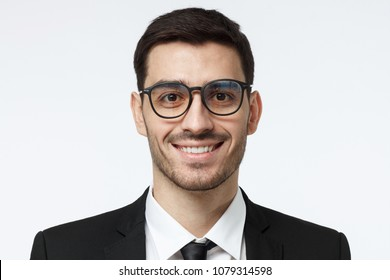 Closeup headshot of young handsome European businessman in glasses pictured isolated on gray background wearing black formal suit, white shirt and tie, looking confident and smiling friendly