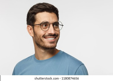 Closeup headshot of young man in round eyeglasses isolated on gray background, smiling happily, looking right, feeling positive, relaxed and joyful