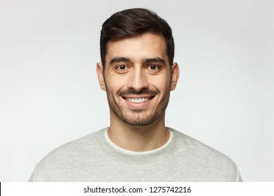 Closeup headshot of young smiling European Caucasian male isolated on gray background