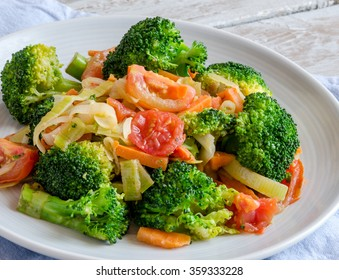 Close-up of healthy breakfast:broccoli, tomatoes, onion, carrot served on white plate