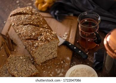 Nahaufnahme eines gesunden mehrkornigen Brotes, das auf einem Holzfußboden geschnitten ist, und eines Holztischs, umgeben von Küchenutensilien und einem Glasteakup