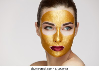 Closeup Of Healthy Young Woman With Gold Cosmetic Face Mask On Soft Skin.