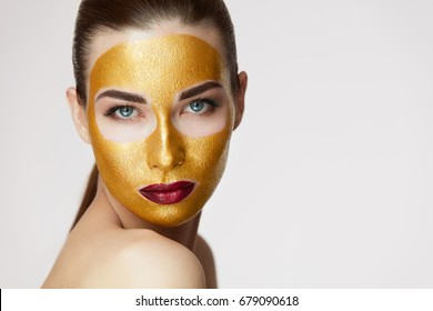 Closeup Of Healthy Young Woman With Gold Cosmetic Face Mask On Soft Skin