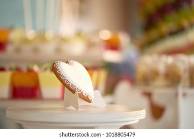 Close-up of a heart-shaped glazed cookie standing on the wooden stand near the candybar with different desserts like cupcakes and jellies. festive choice gor wedding celebration.