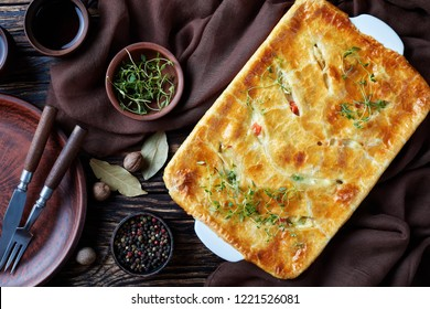 close-up of hearty Homemade Chicken Pot Pie with Peas, celery and Carrots in a baking dish on an old rustic table with brown cloth and spices, view from above, flatlay