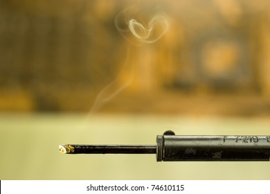 closeup of heated soldering iron with smoke on blurred background