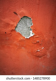 closeup of heavily weathered and damaged pealing earth red coloured paint on ancient plastered wall