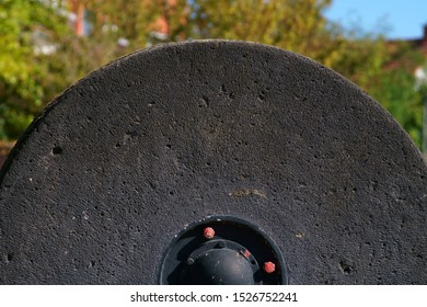The close-up of a heavy millstone.