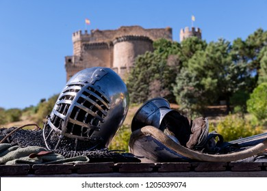 Close-up of a helmet and protective gloves for medieval combat, and in the background a castle