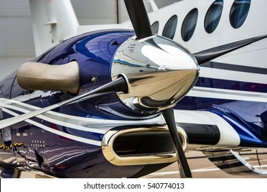 Closeup high detailed view of engine and airscrew of modern turboprop airplane standing on parking place at airport.