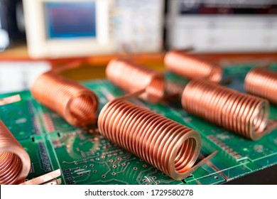 Close-up of high-frequency copper wire on green microcircuit on background of numerous blurry computers. Concept production of super modern high-tech components for transceiver appliances