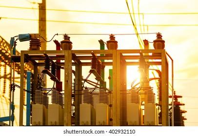 Close-up of high-voltage power substation equipment, evening landscape.