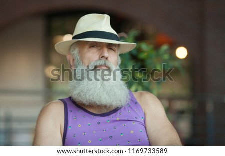 Closeup of hipster old man with beard and mustache wearing purple shirt and  straw fedora hat 095bcecc84b2