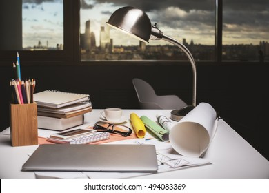 Closeup of hipster workplace with closed laptop, tablet lamp, documents and supplies in interior with city view at dusk