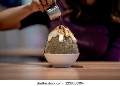 Closeup hojicha Bingsu on tray, Bingsu or Bingsoo, Korean shaved ice dessert with sweet toppings and fruit and varieties with ingredients, popular dessert, using as a background or wallpaper