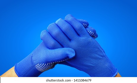 Close-up Holding Hands in Blue Gloves Isolated on Blue Background